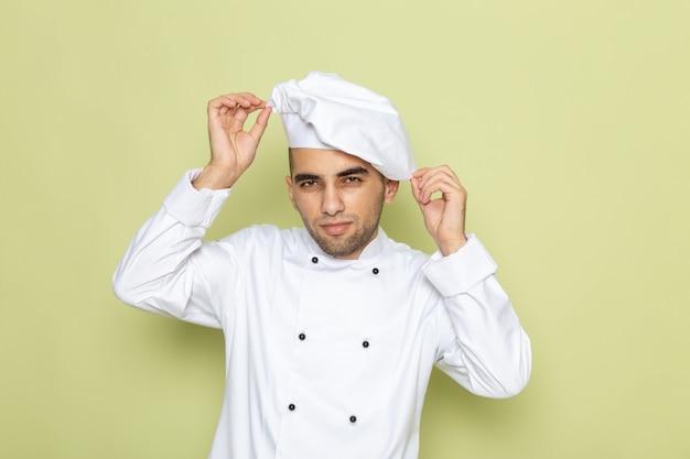 Vue De Face Jeune Homme Cuisinier En Costume De Cuisinier Blanc Fixant Son Bonnet Blanc Sur Vert Photo gratuit