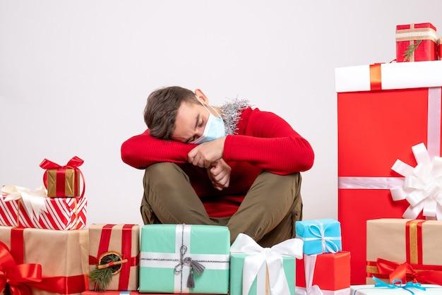 Vue De Face Jeune Homme Avec Masque Dormir Autour Des Cadeaux De Noël Photo gratuit