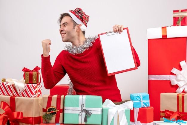 Vue De Face Jeune Homme Montrant Le Geste Gagnant Assis Autour De Cadeaux De Noël Photo gratuit