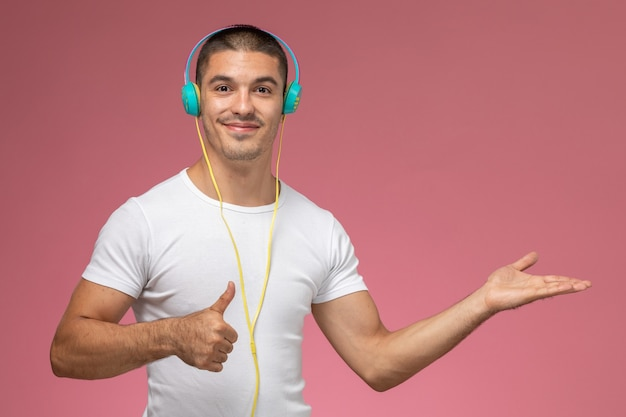 Vue De Face Jeune Homme En T-shirt Blanc, écouter De La Musique Via Ses écouteurs Souriant Sur Fond Rose Clair Photo gratuit