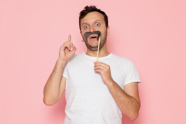 Une Vue De Face Jeune Homme En T-shirt Blanc Tenant Une Fausse Moustache Sur Le Bureau Rose Homme Couleur émotion Pose Photo gratuit
