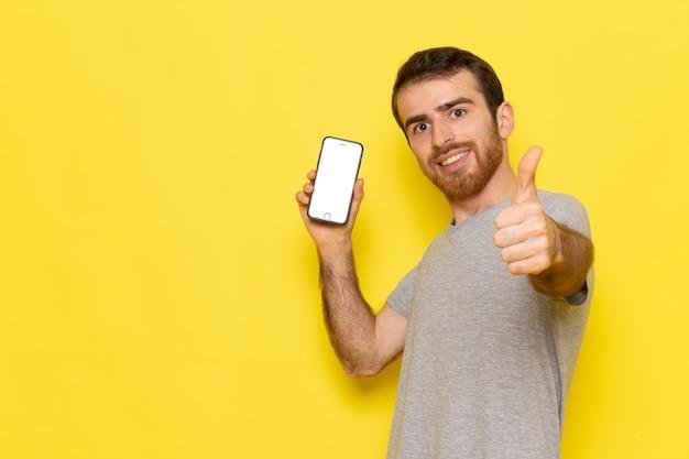 Une Vue De Face Jeune Homme En T-shirt Gris Holding Smartphone Avec Sourire Sur Le Modèle De Couleur Homme Mur Jaune Photo gratuit