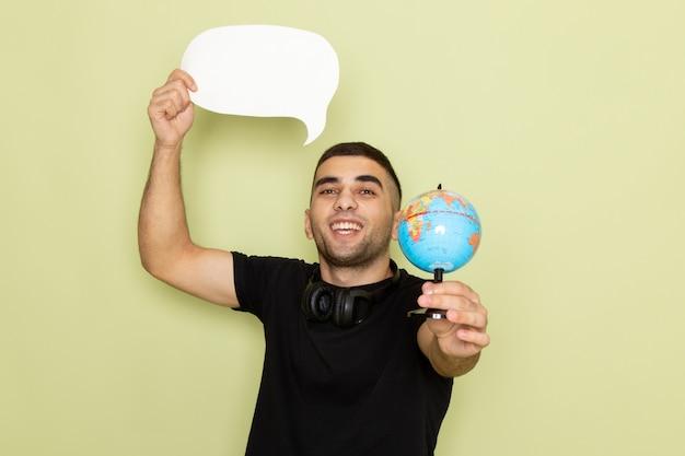 Vue De Face Jeune Homme En T-shirt Noir Tenant Une Pancarte Blanche Et Petit Globe Sur Vert Photo gratuit