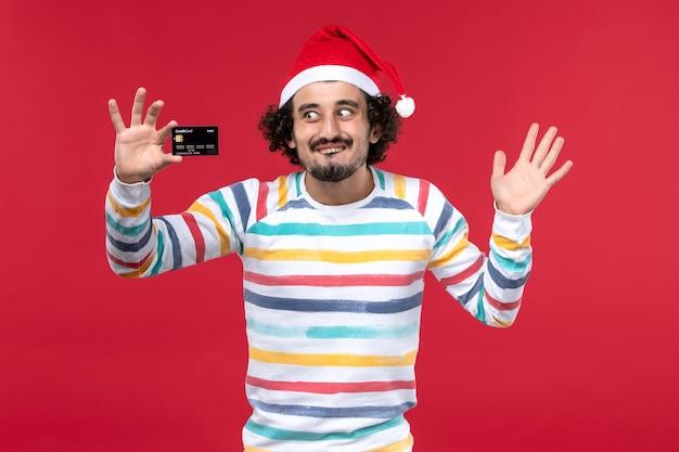 Vue De Face Jeune Homme Tenant Une Carte Bancaire Noire Sur Le Mur Rouge Argent Vacances D'émotion Mâle Rouge Photo gratuit