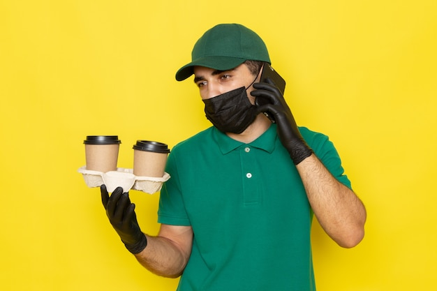 Vue De Face Jeune Messager En Chemise Verte Cap Vert Tenant Des Tasses à Café Et Parler Au Téléphone Sur Jaune Photo gratuit