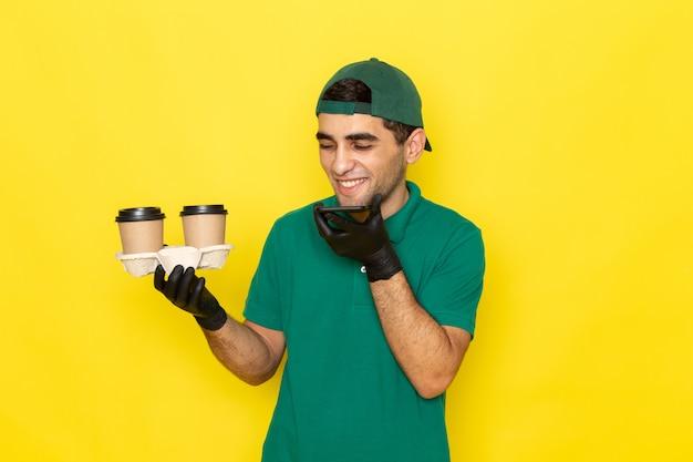 Vue De Face Jeune Messager En Chemise Verte Cap Vert Tenant Des Tasses à Café Et Parler Au Téléphone Avec Rire Sur Jaune Photo gratuit