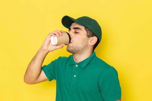 Vue De Face Jeune Messager En Chemise Verte Casquette Verte Boire Du Café Sur Jaune Photo gratuit