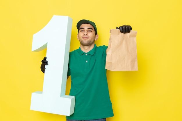 Vue De Face Jeune Messager En Chemise Verte Casquette Verte Gants Noirs Tenant Le Paquet Et Numéro Un Sur Jaune Photo gratuit