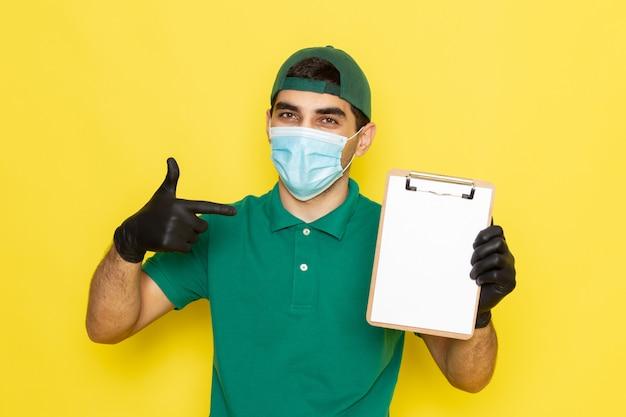 Vue De Face Jeune Messager En Chemise Verte Casquette Verte Tenant Le Bloc-notes Sur Jaune Photo gratuit