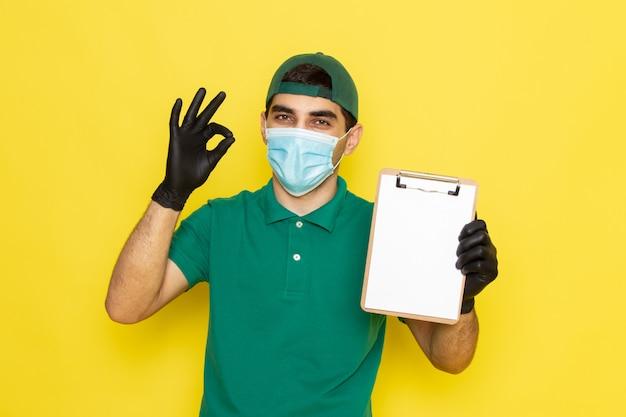 Vue De Face Jeune Messager En Chemise Verte Casquette Verte Tenant Le Bloc-notes Montrant Bien Signe Sur Jaune Photo gratuit