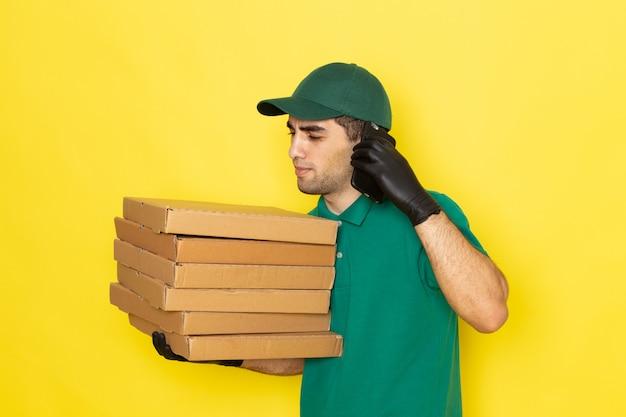 Vue De Face Jeune Messager En Chemise Verte Casquette Verte Tenant Les Boîtes De Livraison Et Parler Au Téléphone Sur Jaune Photo gratuit