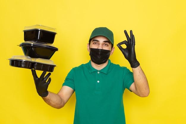 Vue De Face Jeune Messager En Chemise Verte Casquette Verte Tenant Des Bols De Nourriture Photo gratuit