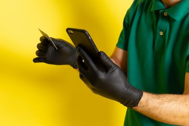 Vue De Face Jeune Messager En Chemise Verte Casquette Verte Tenant Une Carte Blanche à L'aide De Son Smartphone Sur Jaune Photo gratuit