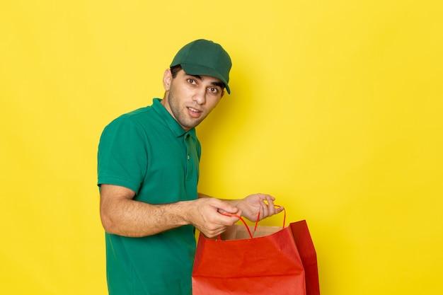 Vue De Face Jeune Messager En Chemise Verte Casquette Verte Tenant Un Paquet D'achat Rouge Sur Jaune Photo gratuit