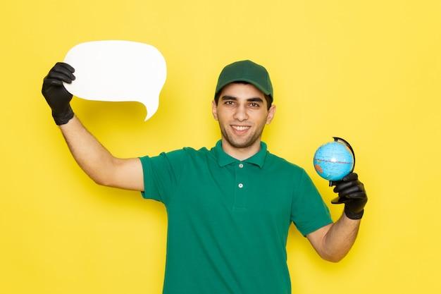 Vue De Face Jeune Messager En Chemise Verte Casquette Verte Tenant Petit Globe Et Panneau Blanc Avec Des Gants Noirs Sur Jaune Photo gratuit
