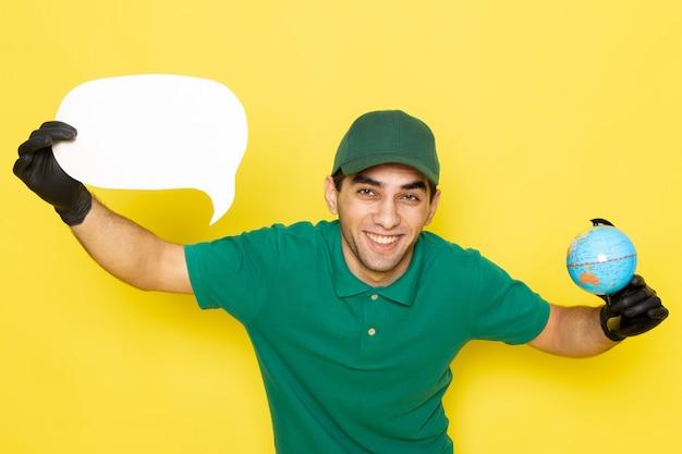 Vue De Face Jeune Messager En Chemise Verte Casquette Verte Tenant Petit Globe Et Panneau Blanc Photo gratuit