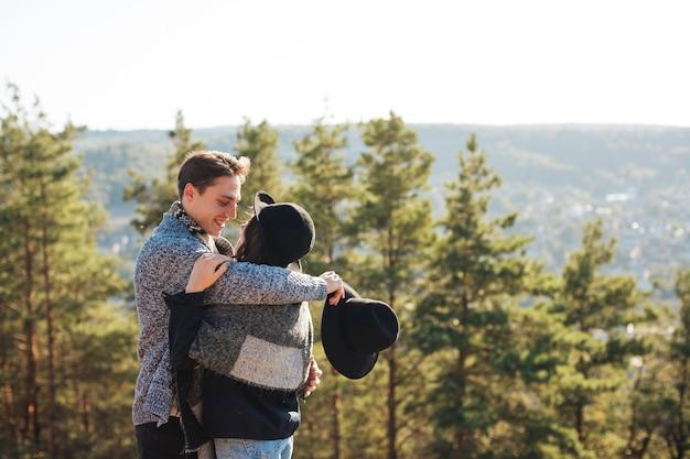 Vue de face joli couple embrassant dans la nature Photo gratuit