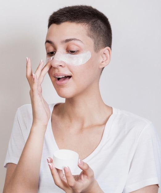 Vue De Face, Jolie Femme Aux Cheveux Courts Avec Une Crème Pour La Peau Photo gratuit