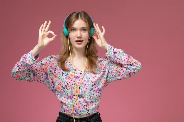 Vue De Face Jolie Jeune Femme Montre Que Tout Va Bien Avec Ses Doigts Et écouter De La Musique Photo gratuit