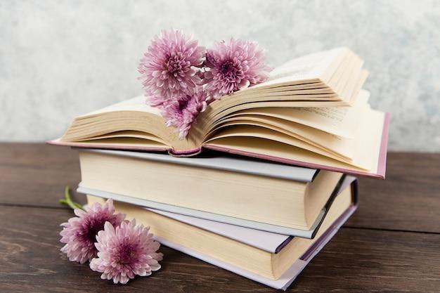 Vue de face des livres et des fleurs sur une table en bois Photo gratuit