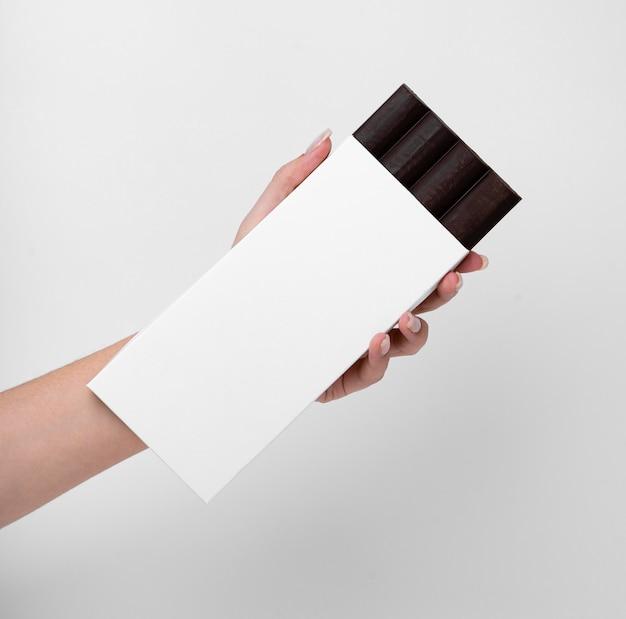 Vue De Face De La Main Tenant La Tablette De Chocolat Avec Emballage Et Espace De Copie Photo gratuit