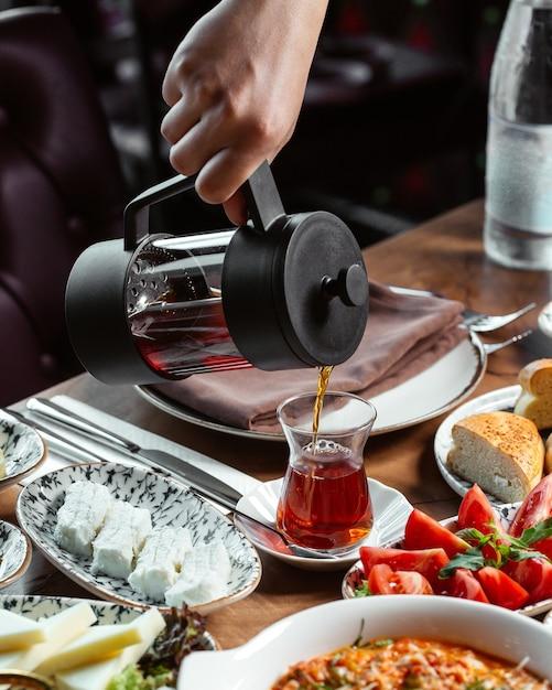 Une Vue De Face Mâle Verser Le Thé Dans Le Petit Déjeuner De Thé En Verre Repas Alimentaire Photo gratuit