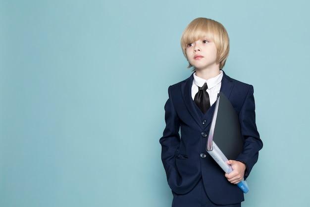 Une Vue De Face Mignon Business Boy In Blue Classic Suit Holding Black Folder Business Work Fashion Photo gratuit