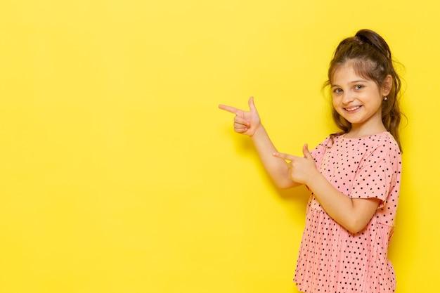 Une Vue De Face Mignon Petit Enfant En Robe Rose Souriant Et Soulignant Photo gratuit