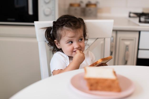 Vue de face mignonne jeune fille sur une chaise Photo gratuit