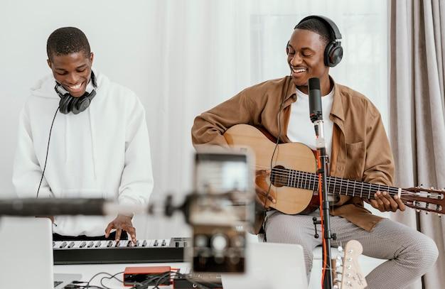 Vue De Face Des Musiciens Masculins à La Maison à Jouer De La Guitare Et Du Chant Photo gratuit
