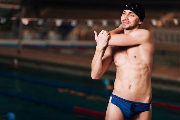 Vue de face d'un nageur s'étendant Photo gratuit