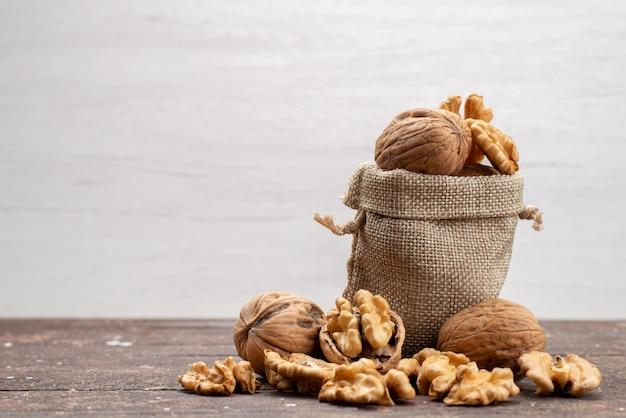 Vue De Face De Noix Entières Fraîches Dans Des Coquilles Et Nettoyées Sur Gris, Snack Noix De Noix Photo gratuit