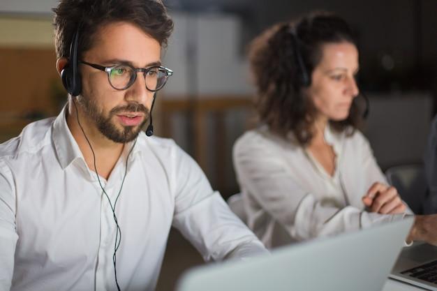 Vue De Face De L'opérateur Du Centre D'appels Communiquant Avec Le Client Photo gratuit