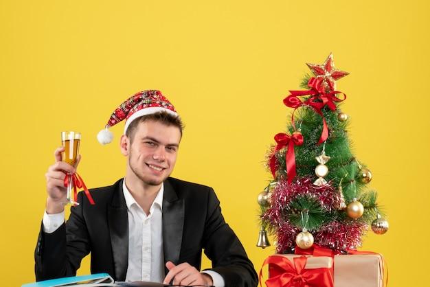 Vue De Face Ouvrier Masculin Célébrant Noël Avec Champagne Autour De Petit Arbre De Noël Et Présente Sur Jaune Photo gratuit