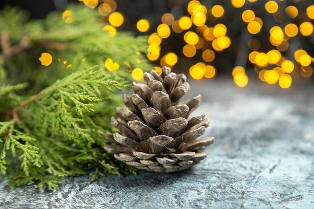 Vue De Face Ouvrir Les Branches De Pin Pomme De Pin Sur Les Lumières De Noël De Surface Isolée Sombre Photo gratuit