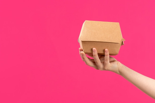 Une Vue De Face Package Hand Holding Brown Package Femelle Main Couleur De Fond Rose Manger De La Nourriture Photo gratuit