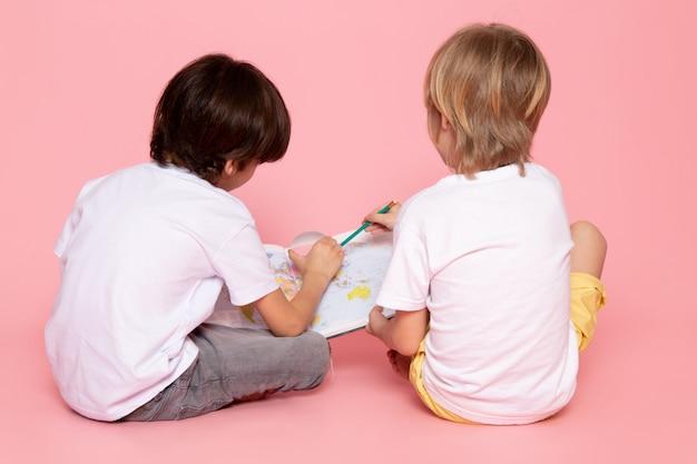 Vue De Face Paire De Garçons Dessin Carte En T-shirt Blanc Sur Rose Photo gratuit