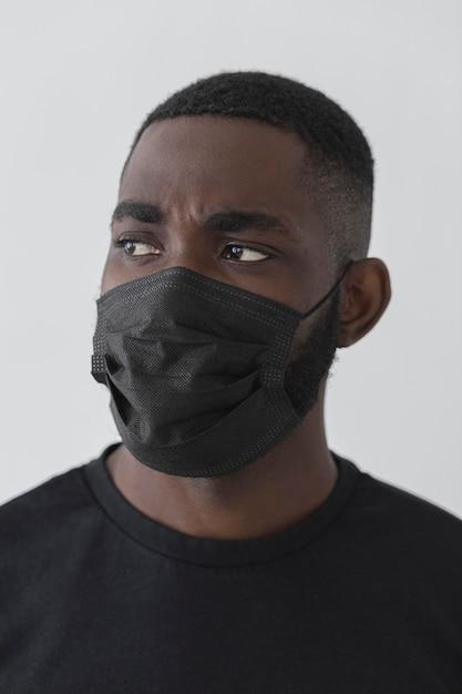Vue De Face Personne Noire Portant Un Masque Et Regardant Ailleurs Photo gratuit