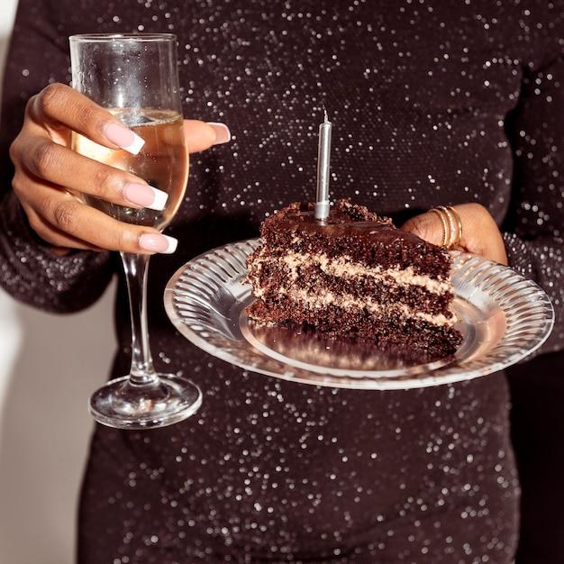Vue De Face Personne Tenant Le Gâteau Et Le Champagne Photo gratuit