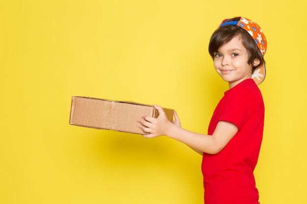 Une Vue De Face Petit Garçon En T-shirt Rouge Casquette Colorée Et Pantalon Kaki Holding Box Sur Le Fond Jaune Photo gratuit