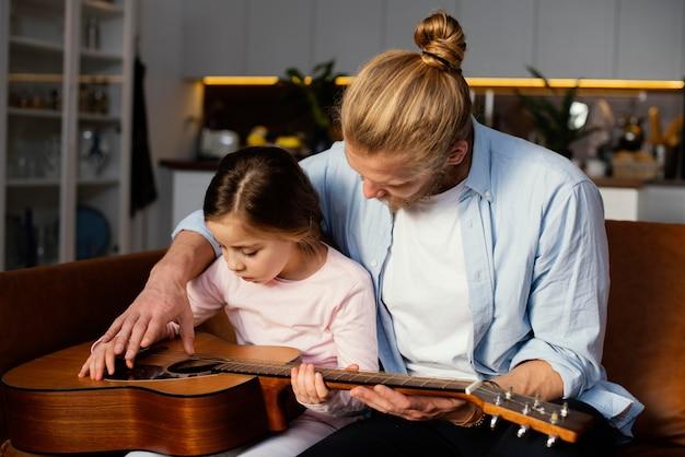 Vue De Face De La Petite Fille Et Du Père Jouant De La Guitare Ensemble Photo gratuit