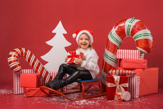 Vue De Face Petite Fille Entourée De Cadeaux De Noël Et D'éléments Photo Premium