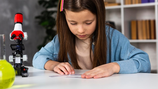 Vue De Face De La Petite Fille Avec Microscope Et Tubes à Essai Photo Premium