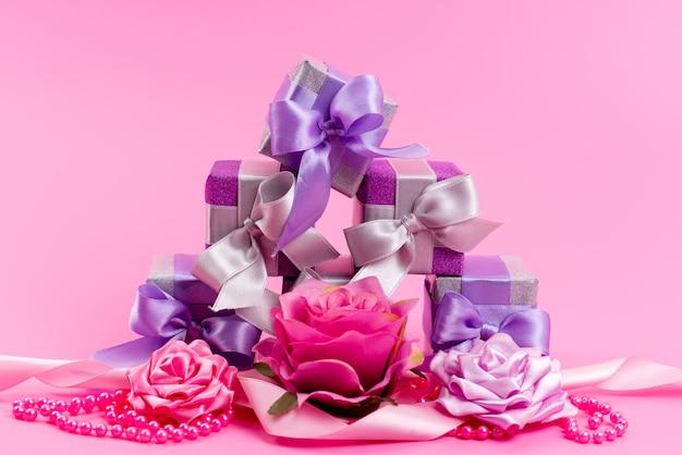 Une Vue De Face De Petites Boîtes Violettes Avec De Petites Fleurs Conçues Sur Rose, Cadeau D'anniversaire Cadeau Photo gratuit