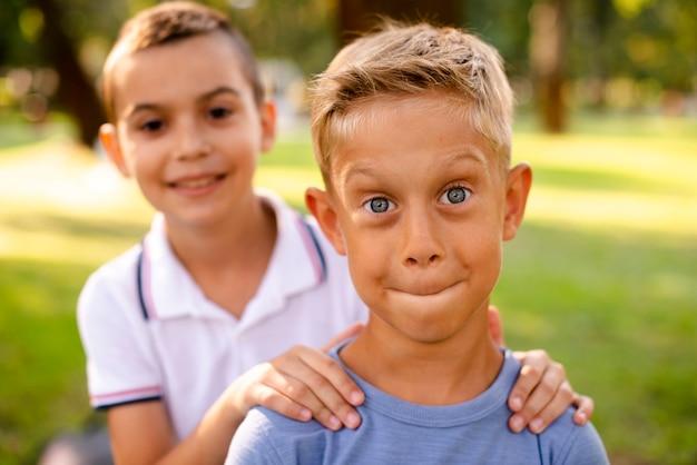 Vue de face des petits garçons faisant des grimaces idiotes pour la caméra Photo gratuit