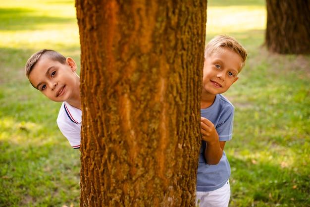 Vue de face des petits garçons posant derrière un arbre Photo gratuit