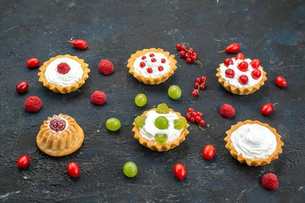 Vue De Face Petits Gâteaux Délicieux Avec De La Crème Et Des Fruits Frais Sur Le Cookie Biscuits Aux Fruits De Bureau Noir Photo gratuit