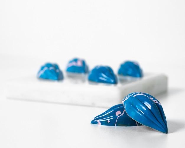Vue De Face Des Pierres Bleues Sur Et à L'extérieur De L'éponge Blanche Sur Le Bureau Blanc Photo gratuit