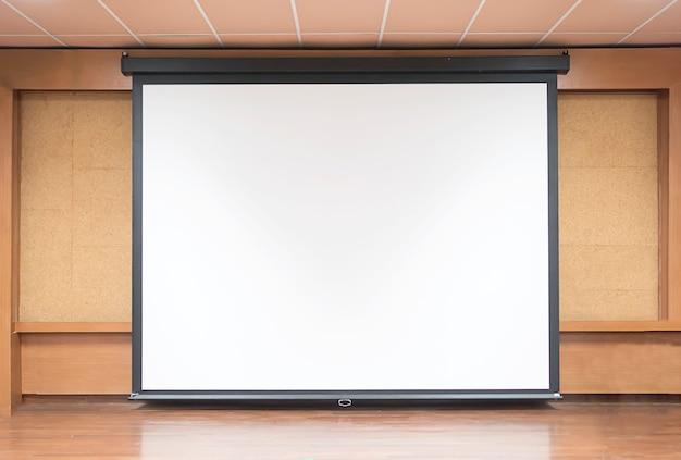 Vue de face de la salle de conférence avec écran de projection blanc vide Photo gratuit