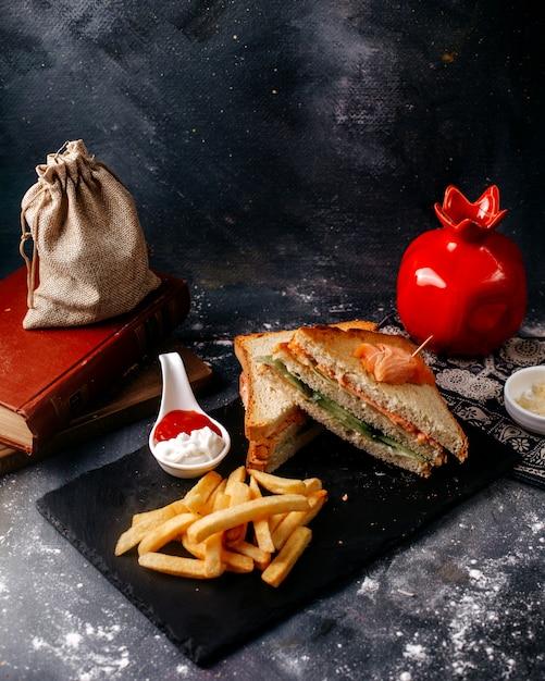 Vue De Face Des Sandwichs Tranchés Avec Des Frites Sur Le Bureau Noir Et Le Sol Gris Photo gratuit
